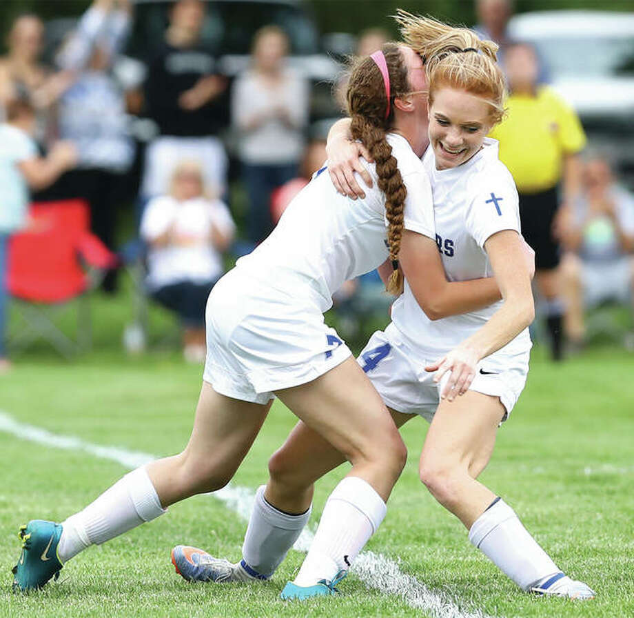 Marquette's Rebekah Johnes, right, is home after a hospital stay following surgery to repair internal injuries suffered in the 2A regional championship game May 19 in Jacksonville. Above, she celebrates a goal last season with teammate Lauren Walsh. Photo: Telegraph File Photo