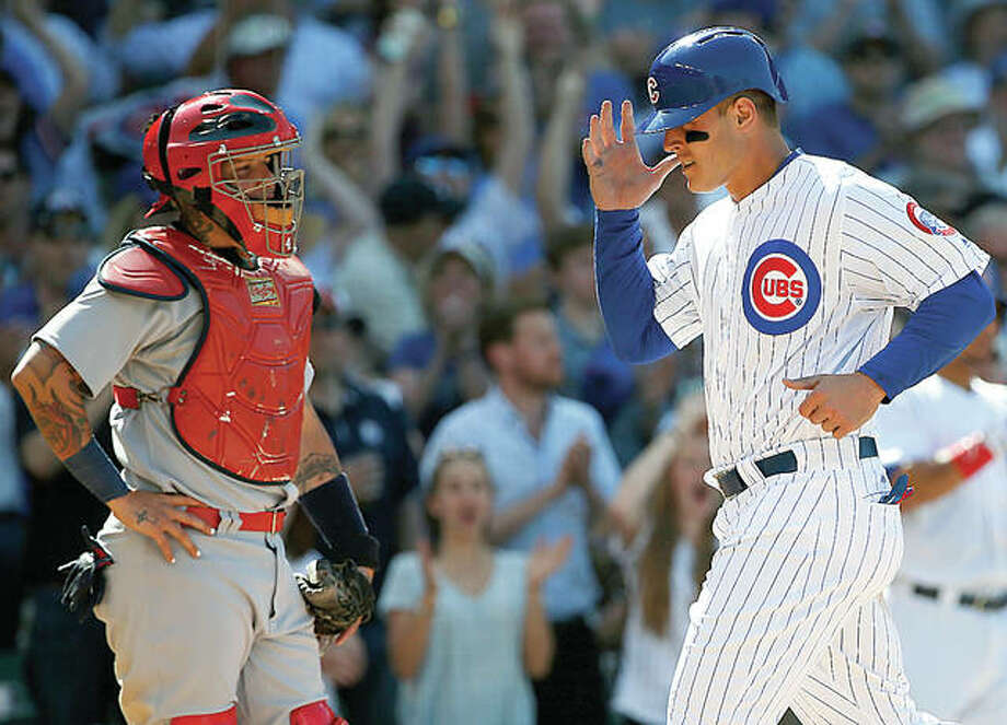 The Cubs' Anthony Rizzo, right, scores on a sacrifice fly by Jason Heyward as Cardinals catcher Yadier Molina looks to the field in the eighth inning Friday's game in Chicago. Photo: AP