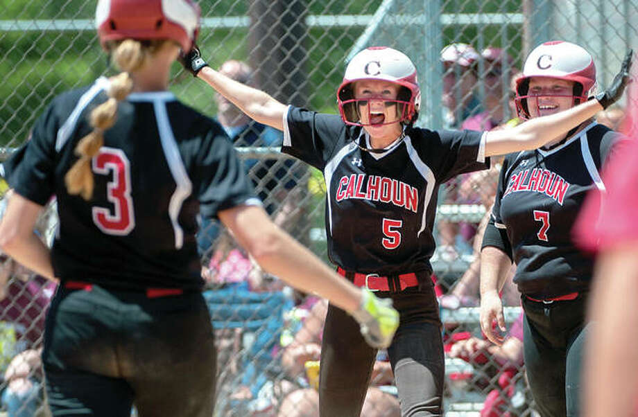 Calhoun's Grace Baalman (3), Junie Zirkelbach (5) and Macy Margherio celebrate their 2-1, 12-inning victory over Princeville after Zirkelbach scored the winning run in the Class 1A softball state semifinal Friday at EastSide Centre in East Peoria. Baalman was on base behind Zirkelbach and Margherio was on deck when Emily Baalman ended it with a walk-off double. Photo: Matt Dayhoff, Peoria Journal-Star | For The Telegraph
