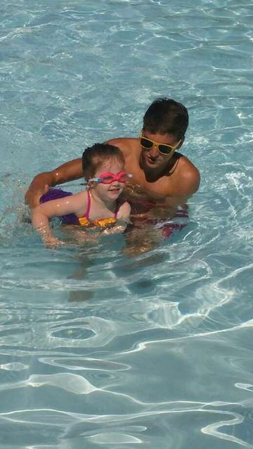 Maddy Cronin, 4 years old, is assisted by Donor Pool's swim aid, Alex Roth, on the second day of Session I Group Swim Lessons on June 6. Photo: For The Telegraph