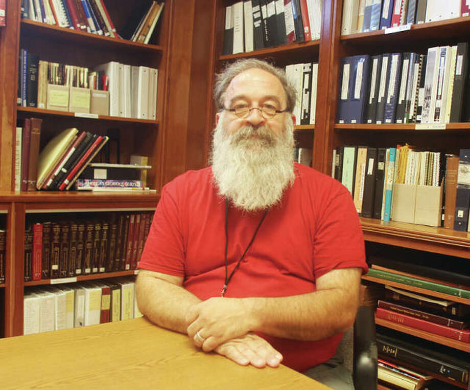 Jon Parkin, the new superintendent at the Madison County Historical Society Museum & Archival Library, sits in front of some of the reference books in the library Tuesday. Parkin, who will retire after 23 years of teaching in the Edwardsville School District at the end of summer school, took over for Suzanne Dietrich, who retired in November. Photo: Scott Cousins | The Telegraph