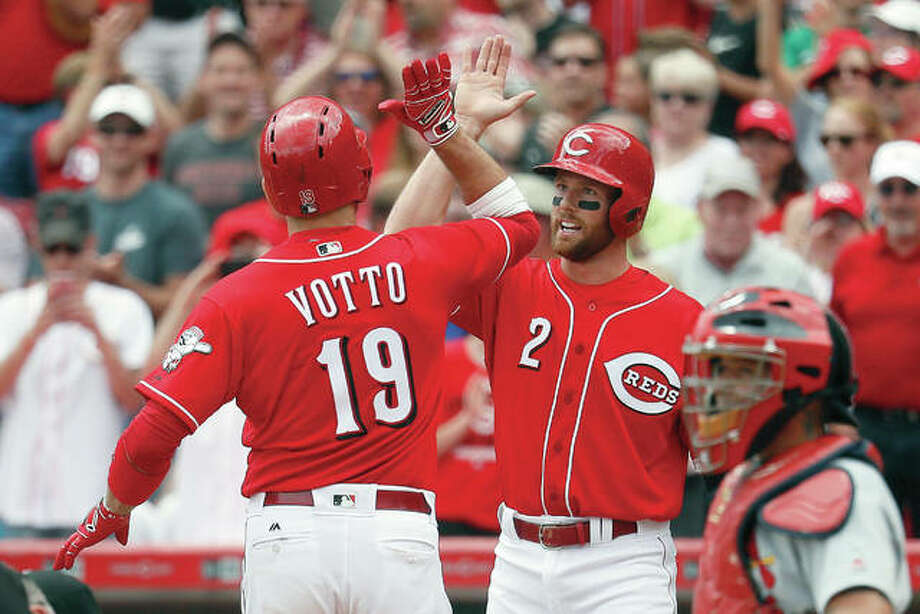 The Reds' Joey Votto (19) celebrates with Zack Cozart (2) after hitting a two-run homer off Cardinals relief pitcher Tyler Lyons in the sixth inning Thursday in Cincinnati. Photo: AP