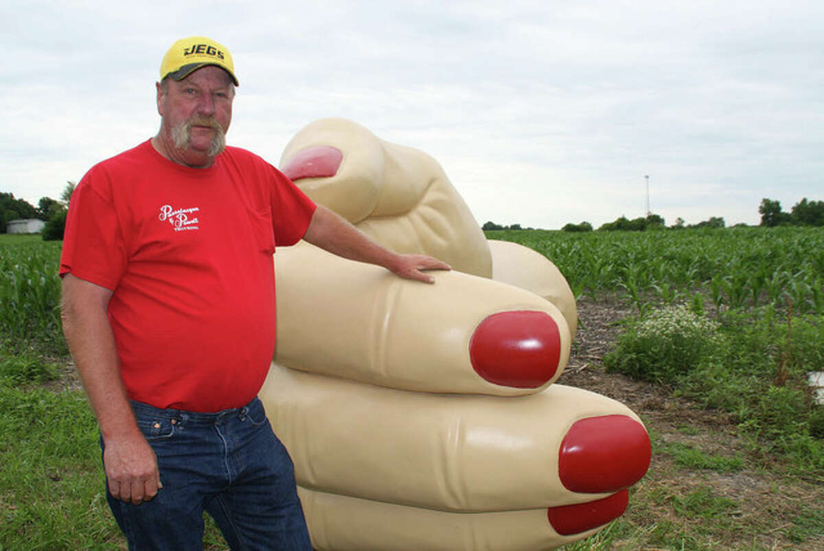 Tony Reid   Herald & Review (AP) Joe Coleman rests a loving hand his giant hand sculpture near Pana. Coleman plans to use the hand as a distinctive landmark, pointing the way to his giant man cave and fundraising party venue, the Corvette Shed west of Pana. It's very hard to miss, measuring 18 feet long from the tips of its ruby-painted nails to its wrist, with a palm area that is 6 feet wide, and tipping the scales at 1,000 pounds.