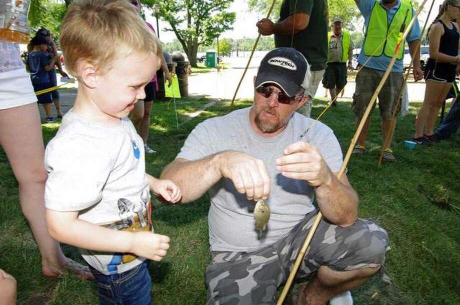 Three-year-old Brantley Ruebush of Pittsfield and his father Blake react after Brantley caught a bluegill during Saturday's Two Rivers Fishing Fair at Pere Marquette State Park.