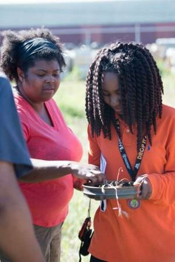 Dr. Danielle Lee, a visiting assistant professor in the College of Arts and Sciences' Department of Biological Sciences (left) and Makyla Green, SIUE Upward Bound student, survey a frog that students discovered during an environmental research project, funded by CAS' Targeted Funding Initiative.