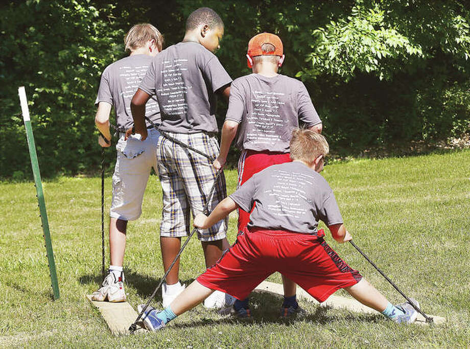 John Badman|The Telegraph A team of participants in the Madison County Sheriff's Department's Sheriff's Academy, held at Camp Warren Levis in Godfrey, found teamwork can be a hard thing as four team members try walking together on two boards. The member on the end did the splits trying to stay on board but landed on his backside. Teamwork and an introduction to other aspects of law enforcement were the theme of the day Monday.