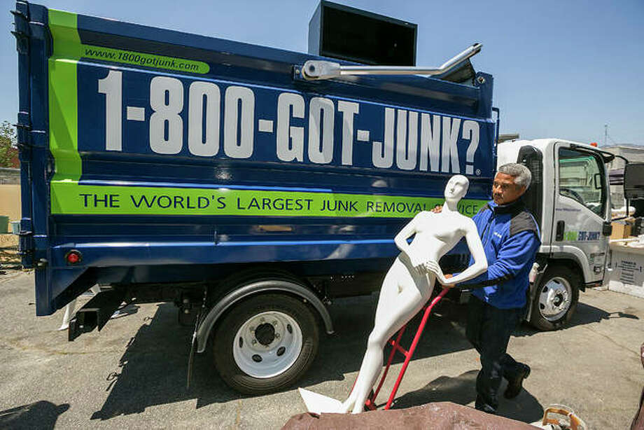 In this Friday, Jun. 9, 2017, photo, 1-800-GOT-JUNK? business owner James Williams gets ready to load a store mannequin into a truck at the business, in Burbank, Calif. Removing the contents of a store is just one part of the job, says Williams. His company also donates usable equipment like vacuum cleaners to charities and takes furniture and fixtures to businesses that will recycle everything that's usable. Williams estimates that he's handled about two store closings a year during the nearly 12 years he's owned the franchise. But there's also a downside for his business when a store closes…he's just lost a customer. Photo: AP Photo/Damian Dovarganes