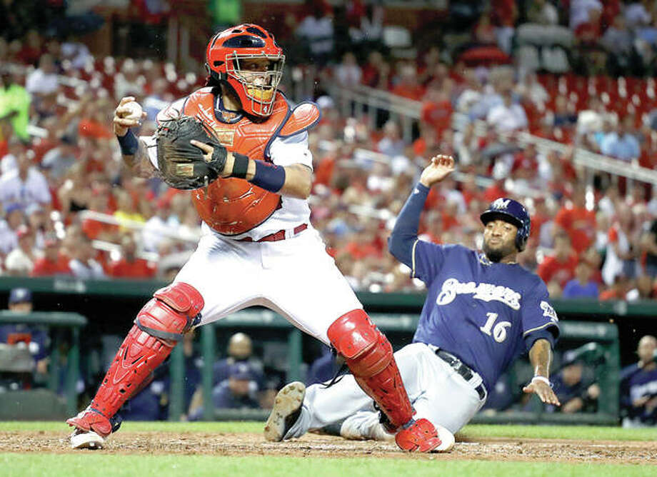 The Brewers' Domingo Santana (16) scores as Cardinals catcher Yadier Molina looks to throw during the seventh inning Wednesday night in St. Louis. Photo: AP