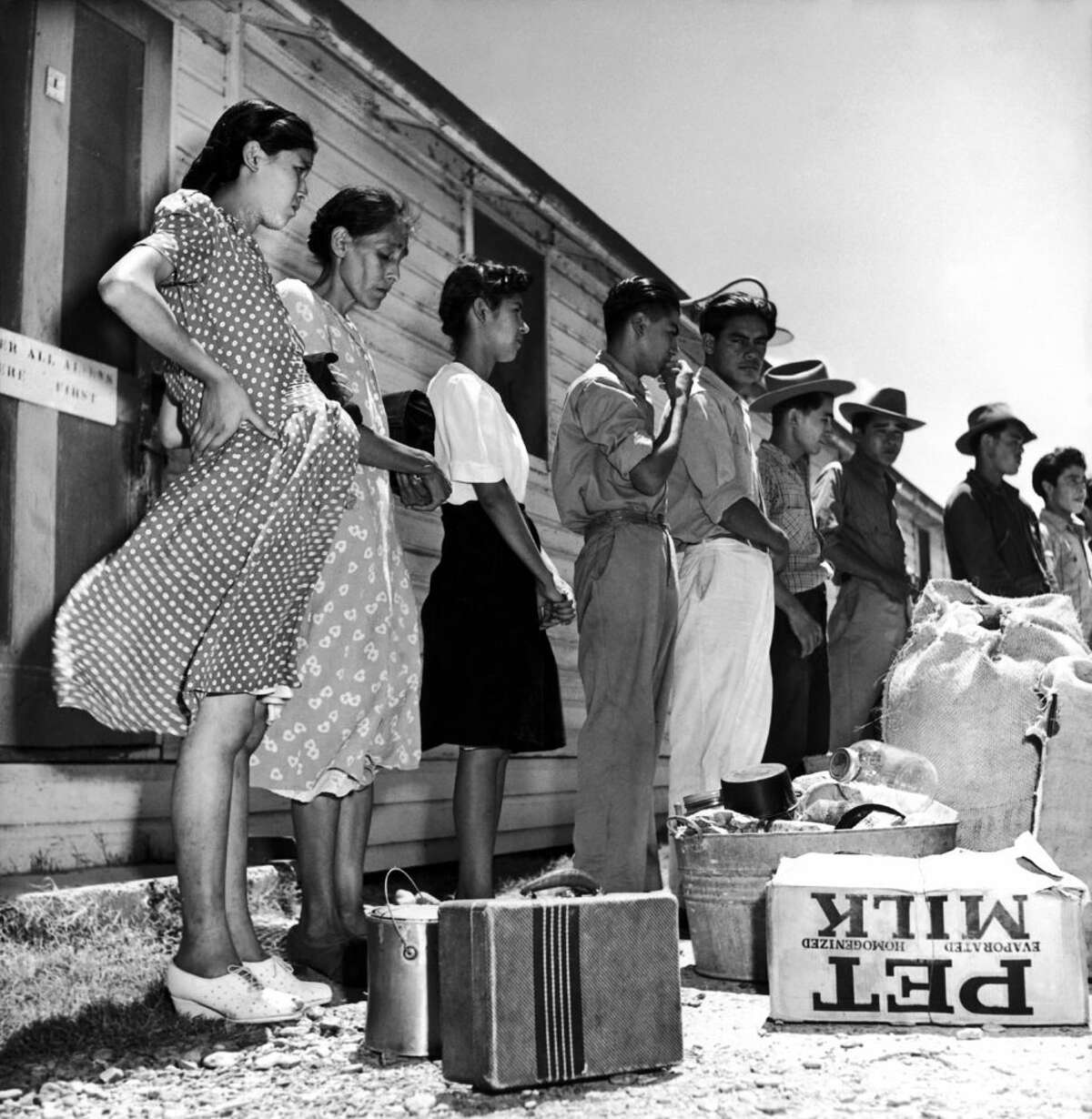 Migrants, including a pregnant woman, wait for inspection to cross the U.S.-Mexico border, circa 1950s.