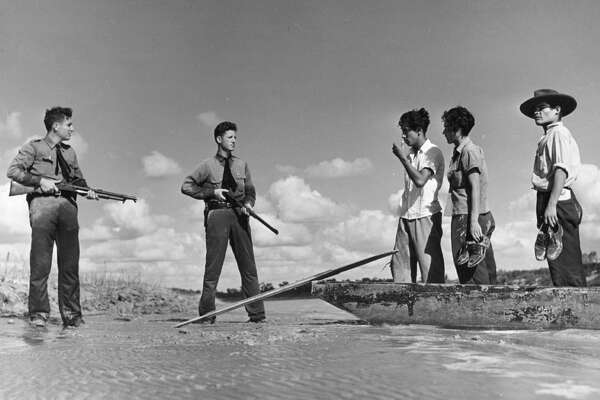 In this 1948 photo, two armed American border guards deterred a group of undocumented immigrants from crossing a river into the U,S.