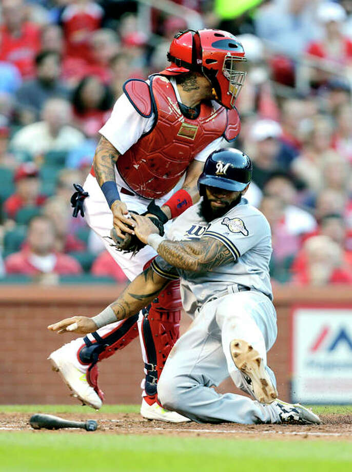 Milwaukee's Eric Thames is tagged out at home by Cardinals catcher Yadier Molina as he tried to score from second on a single by Travis Shaw during the fifth inning Thursday at Busch Stadium. Thames later hit the game-winning home run in the nonth inning of his team's 6-4 win. Photo: AP