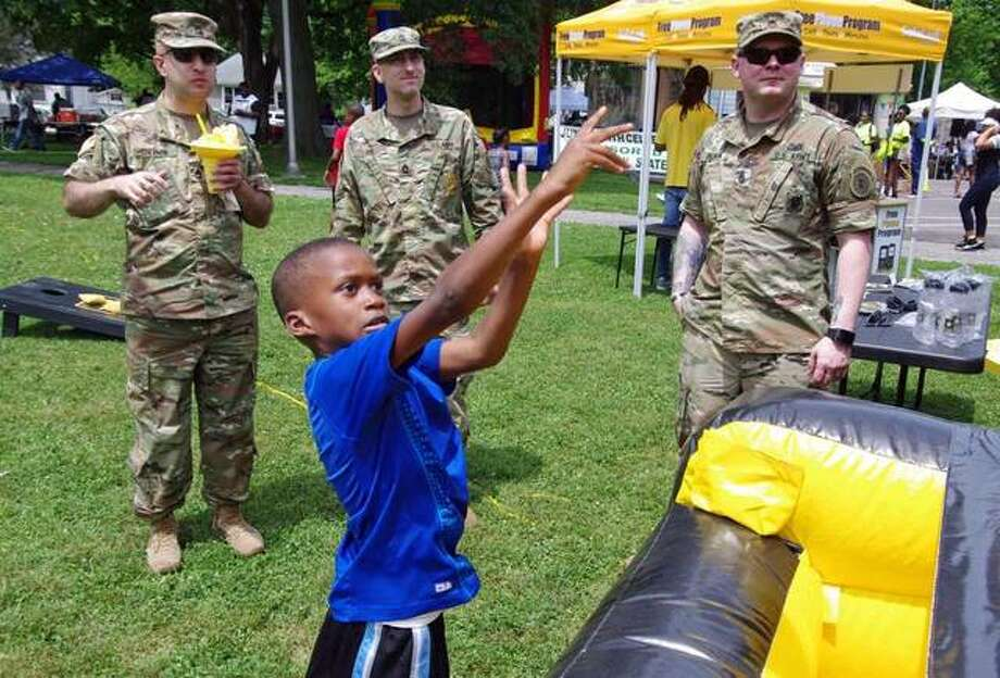 A young visitor tries his hand at the basket game operated by the United States Army Recruiters during Saturday's Juneteenth Celebration. Photo: David Blanchette For The Telegraph