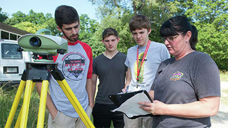 A representative from IDOT instructs campers on land surveying.