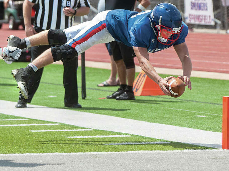The West's Jacob Dixon of Carlinville dives into the end zone for a touchdown during a 58-7 win over the East in the 43rd Illinois Coaches Association High School Shrine Game Saturday at Illinois Wesleyan's Tucci Stadium in Bloomington. Photo: Photo By Lewis Marien, Bloomington Pantagraph