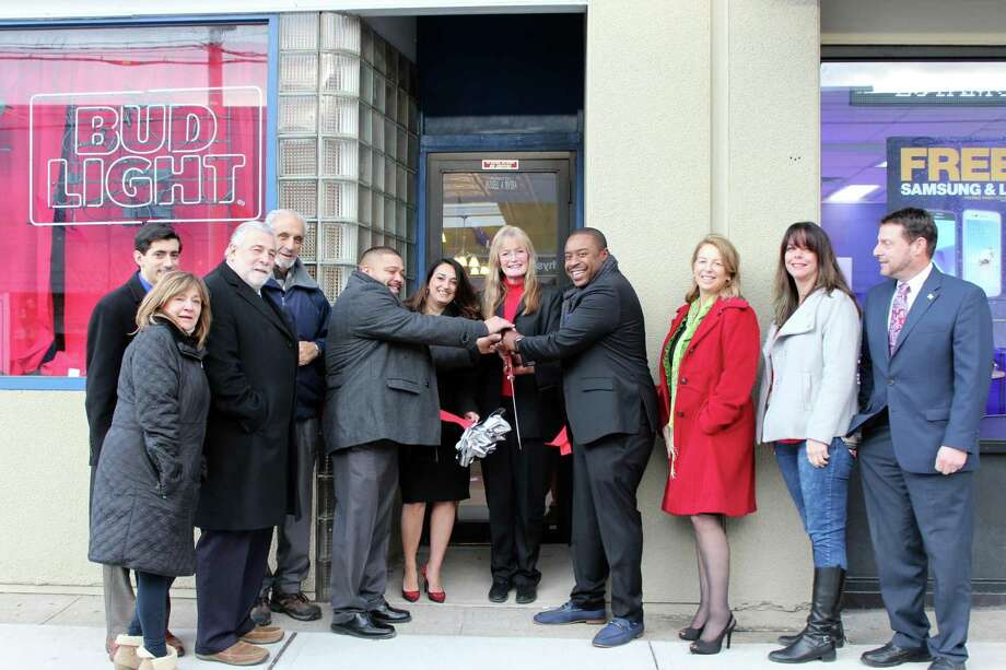 The Spot Opens: West Haven Mayor Nancy R. Rossi, holding a pair of oversize scissors, cuts the ceremonial ribbon Feb. 2 with Russell Rivera and Lonnie Edwards, owners of The Spot Bar and Grill, to mark the restaurant's grand opening at 555 Campbell Ave., formerly Stevie B's. Joining the celebration are, from left, state Rep. Michael A. DiMassa, D-West Haven; City Clerk Deborah Collins; state Rep. Charles J. Ferraro, R-West Haven; mayoral Executive Assistant Louis P. Esposito Jr.; The Spot General Manager Richelle Virzi; state Rep. Dorinda Borer, D-West Haven; Councilwoman Bridgette J. Hoskie, D-1; and City Council Chairman Ronald M. Quagliani, D-At Large. The new downtown business serves lunch and dinner and offers daily food and drink specials. The kitchen is open noon-10 p.m. Sunday to Thursday and noon-midnight Friday and Saturday. Photo: Contributed / City Photo / Michael P. Walsh