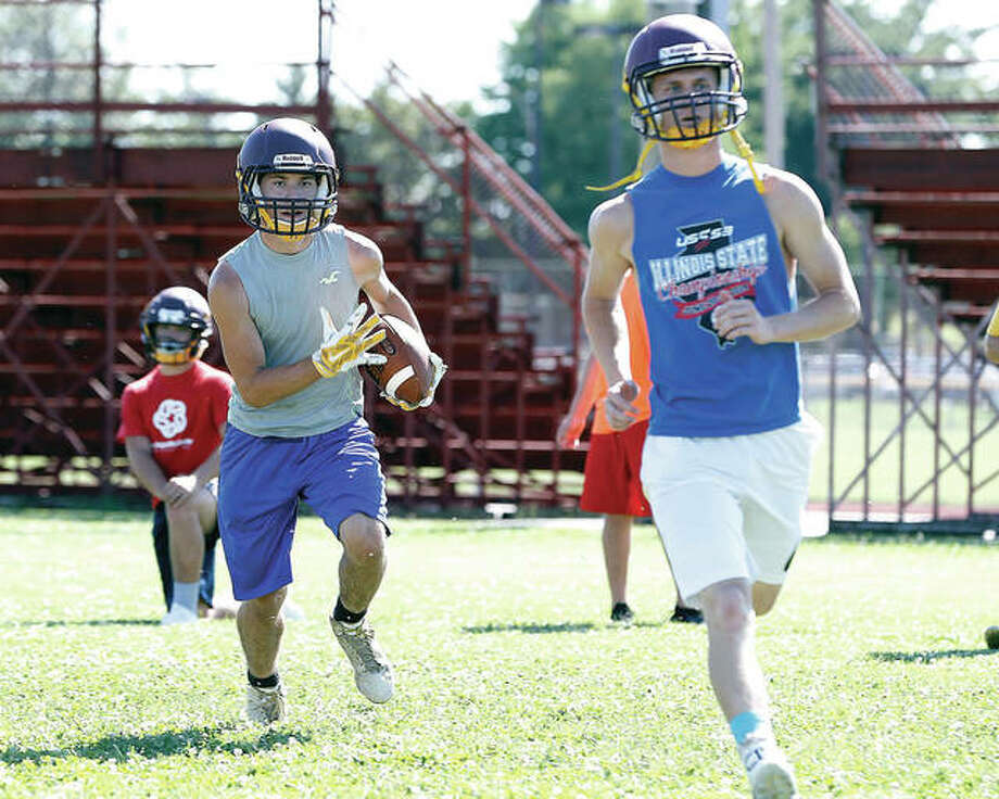 EA-WR Oilers senior Brayden Young, left, runs the ball as senior Justin Englar, right, lead blocks during a summer camp workout on Tuesday in Wood River. Photo: Billy Hurst | For The Telegraph