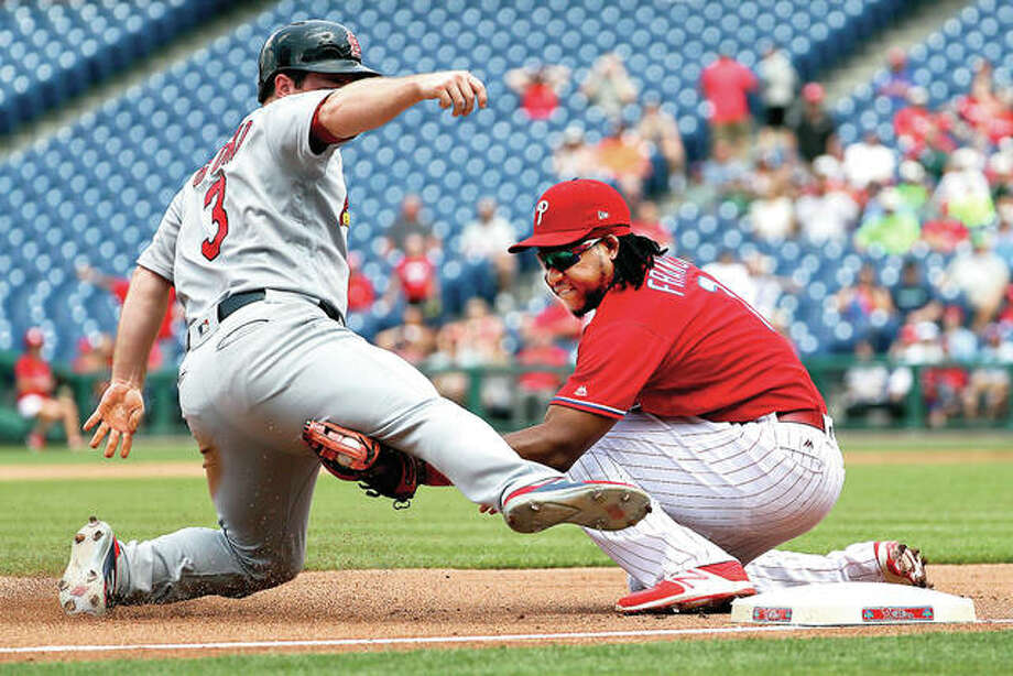 The Cardinals' Jedd Gyorko, left, is tagged out by Phillies third baseman Maikel Franco after Gyorko tried to advance to third on a dropped fly ball hit by Yadier Molina in the fourth inning Thursday in Philadelphia. Photo: AP