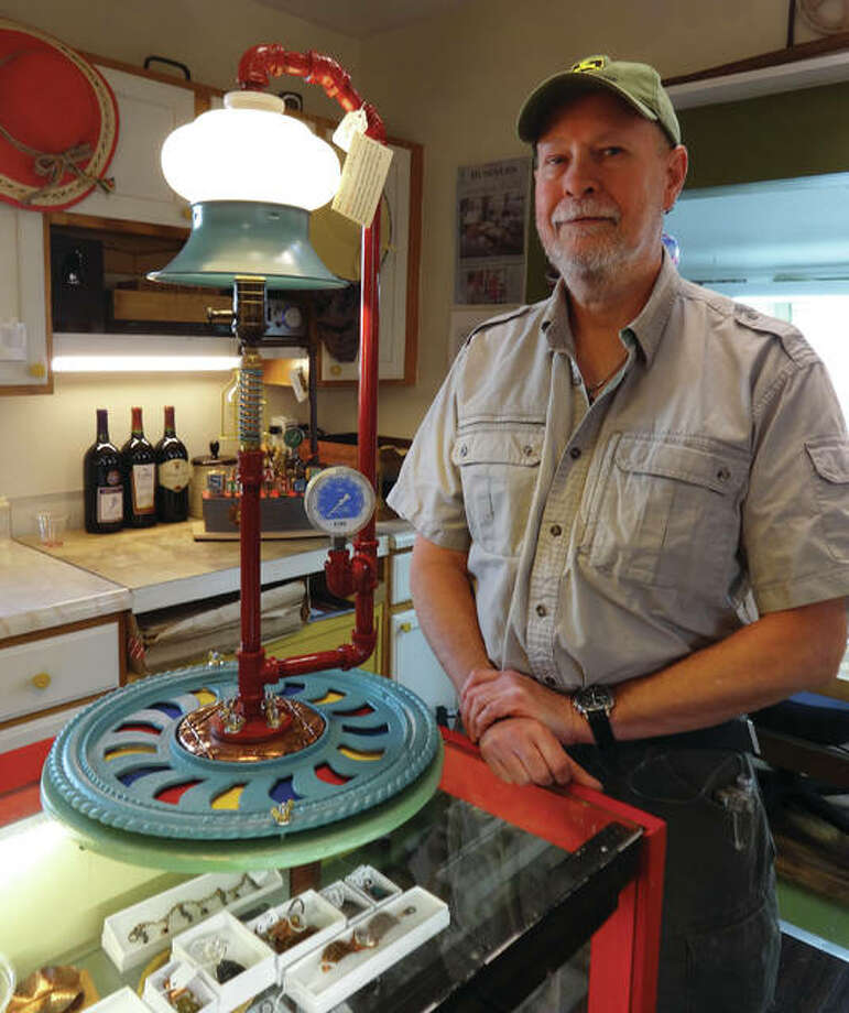 "Buena Vista's co-owner and in-house artist Greg Brummett creates lamps as functional, artistic sculptures, each titled upon completion. He finished one of the shop's latest lighting pieces, shown with Brummett here, on the same day as now defunct Ringling Bros. and Barnum and Bailey Circus' final act — Brummett named the piece ""Circus Endus."" Photo: Jill Moon/The Telegraph"