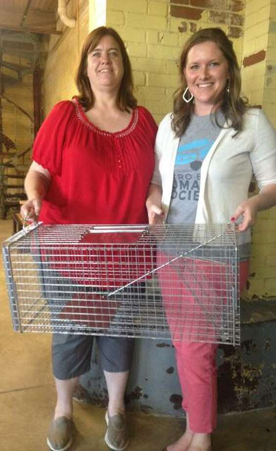 Shelly Moore, Community Cat program coordinator for Metro East Humane Society (left), and Anne Schmidt, executive director of the MEHS, hold one of the new traps to be used in the agency's Community Cat Program's Trap-Neuter-Release program in Alton, beginning in early July. Linda N. Weller/The Telegraph