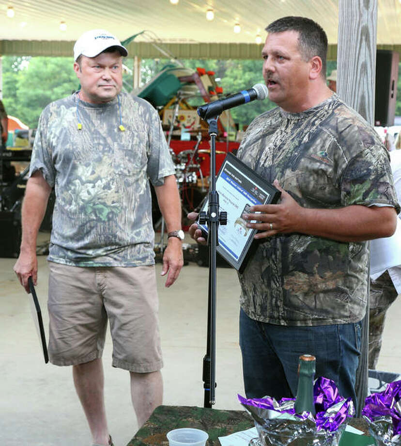 Jason Bowman, EMS manager at Alton Memorial, accepts the Mission: Lifeline EMS Gold Plus Award during the Alton Memorial Health Services Foundation's annual Duck Pluckers Ball on June 3. AMH President Dave Braasch listens at left. Photo: For The Telegraph