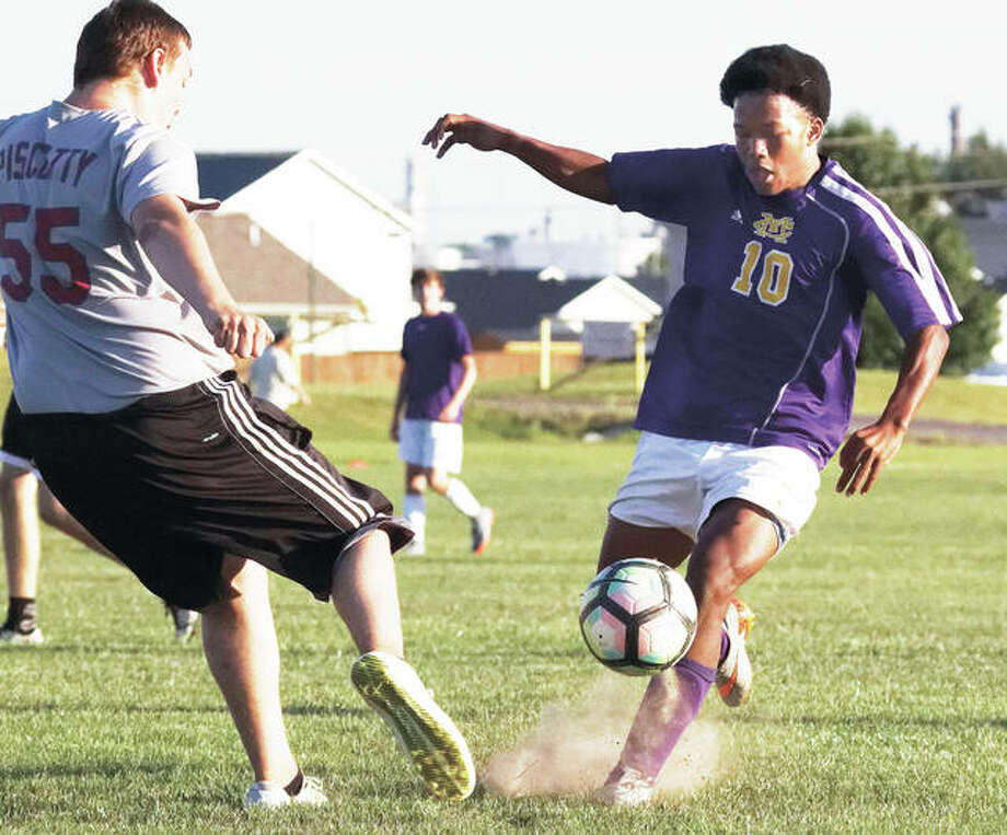 Keante Hardimon (10) of Civic Memorial battles for the ball against East Alton-Wood River's Tommy Forrester during a summer prep soccer scrimmage Tuesday evening at the Wood River Soccer Park. Each Tuesday, teams from East Alton-Wood River, Roxana, CM, Father Givney Catholic and Wesclin high schools play three 25-minute scrimmages in rotation on the fields at the soccer park. The scrimmages are arranged by EA-WR coach Mike Lawson. Along with summer training sessions, they are part of the summer contact days allowed by the Illinois High School Association. Photo: Nathan Woodside | For The Telegraph
