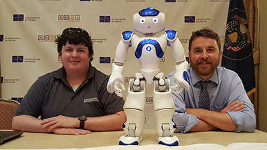 "SIUE graduate student Ehren Wolfe (left), ""Mo"" the humanoid robot (center), and Stephen Hupp, PhD, professor of psychology in the SIUE School of Education, Health and Human Behavior (right). Photo: For The Telegraph"