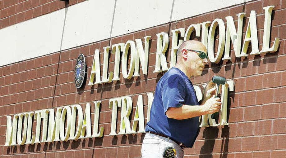 An employee of R.W. Boeker Co., Inc., in Hamel, uses a rubber mallet to tap a T into place for the lettering of the sign on the new Alton Regional Multi-Modal Transportation Center back in late April. The construction of the station itself is mostly finished but a two-month extension on the completion date, to August 31, has been granted for exterior concrete work. Photo: John Badman|The Telegraph