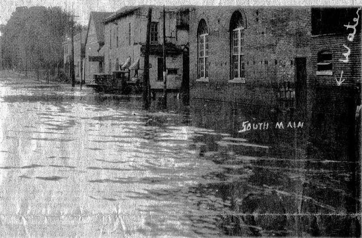 A large portion of Jacksonville resembled a lake in the wake of the great flood of 1926. This photograph shows South Main Street north of the Town Brook. The Illinois Power & Light Corp. plant is in the foreground at right. The buildings to the south housed the McNamara-Heneghan Co.'s Brook Mills, a retail flour and feed business.