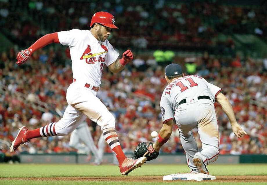 The Cardinals' Tommy Pham, left, is safe at first base as Washington Nationals first baseman Ryan Zimmerman waits for the throw in the seventh inning Friday in St. Louis. Photo: AP
