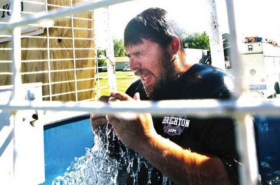 Scott Green, a volunteer firefighter with the Brighton Fire Department, recovers after going for a plunge in the department's dunk tank Saturday at Schnieder Park. The department spent Independence in the Park raising money for the Fill the Boot campaign to benefit MDA.