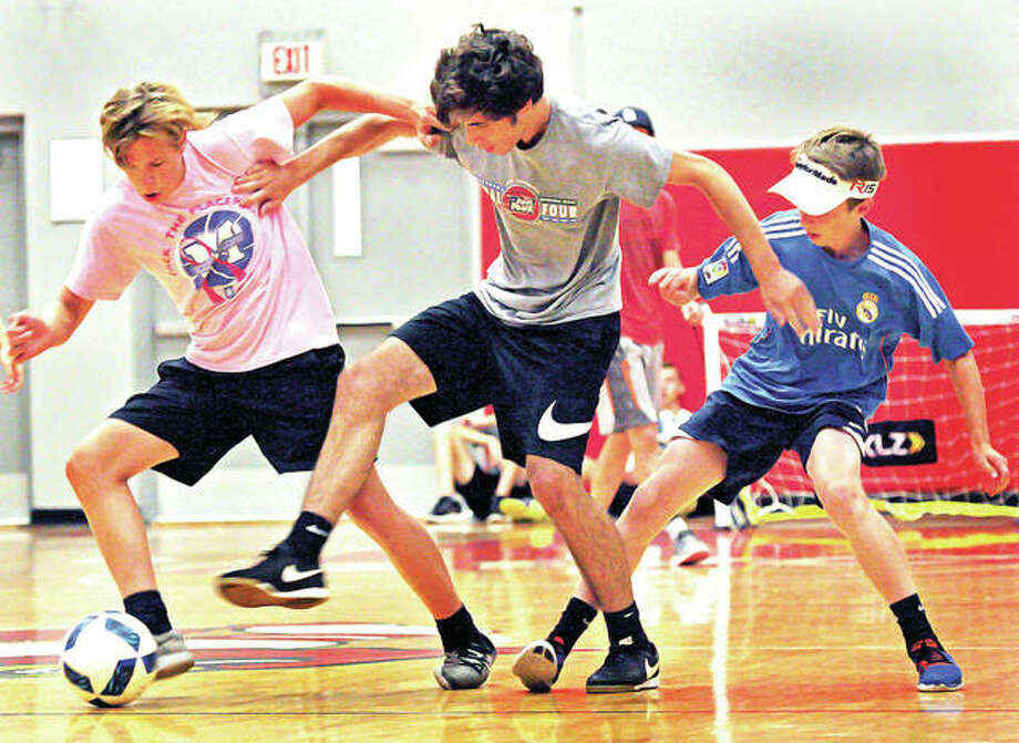 Alton junior Cade Davis, center fends off junior Roman Thomeczek, left, and sophomore Brayden Decker during a summer soccer workout Friday in the AHS gym. Photo: Nathan Woodside | For The Telegraph