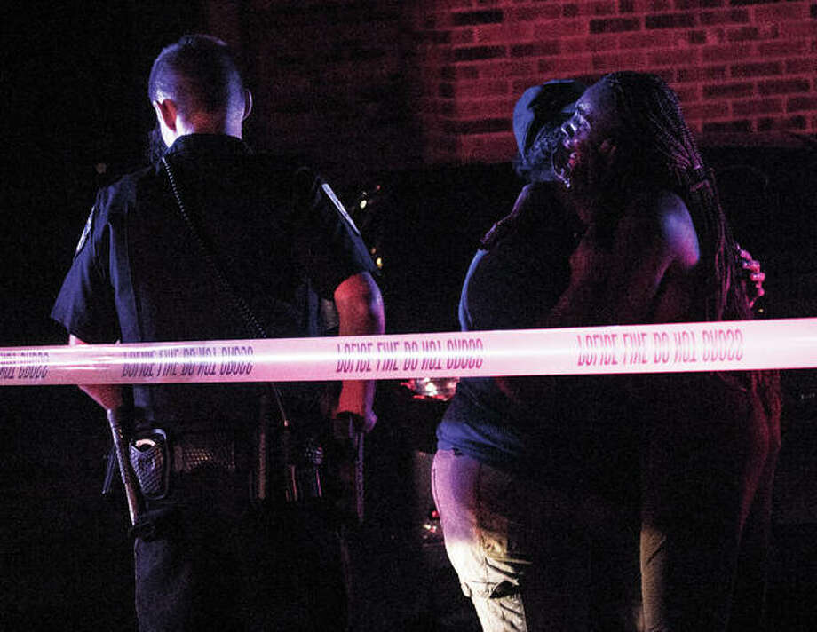 Two women embrace in sorrow early Saturday morning after arriving on the scene of a shooting in the 700 block of Oakwood in Alton. Police were seeking three black males and one white female who fled in a white convertible with Wisconsin license plates. Photo: Nathan Woodside | For The Telegraph