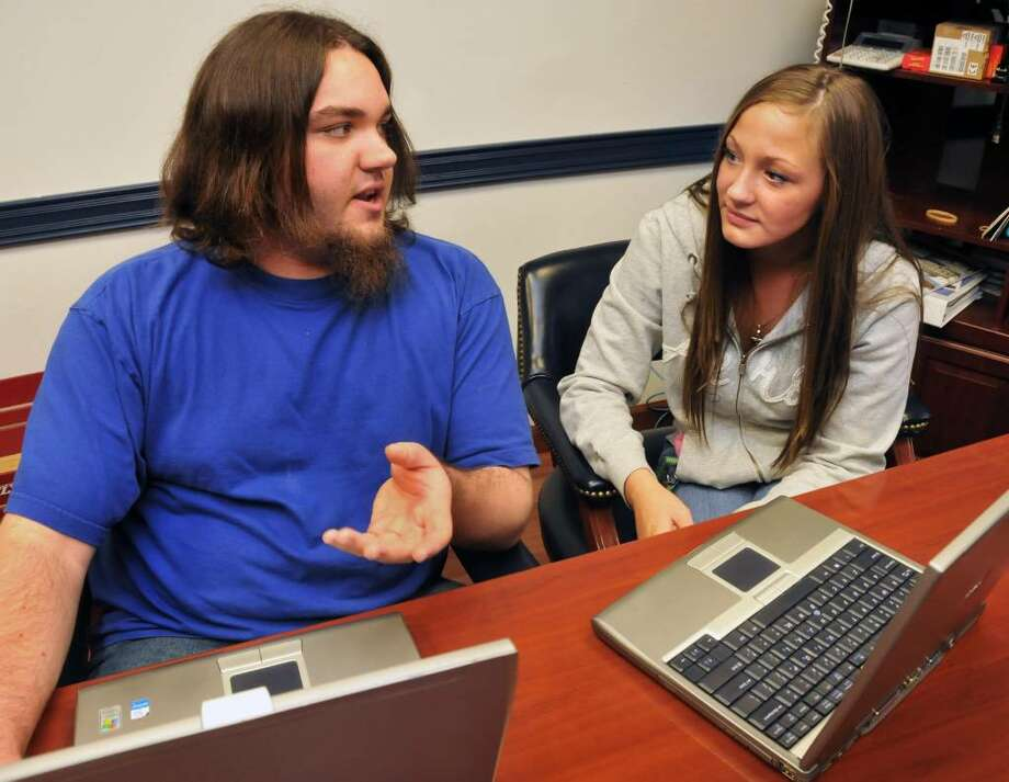HVCC student Eric Bartholomew, 20, left, says a laptop he received from the Watervliet Housing Authority Laptops for Kids program helped him. Janelle Carrigan, 17, will receive a laptop for college. (John Carl D?Annibale/Times Union) Photo: John Carl D'Annibale / 00008734A