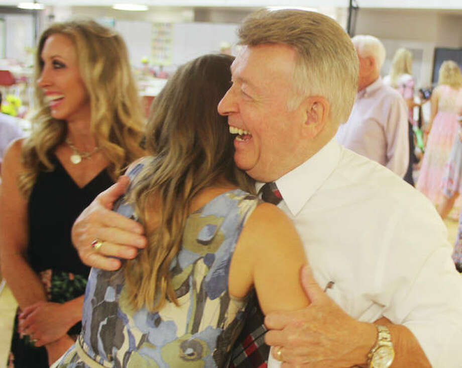 The Rev. Tom Olney hugs family members during a reception at Calvary Baptist Church Saturday afternoon. Olney has stepped down as pastor of Faith Baptist Church in Godfrey after 52 years.