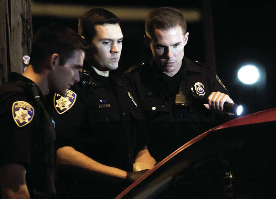 Alton police officers speak to the occupants of a vehicle early Sunday morning at Midtown Restaurant and Bar, 1026 E. 7th St., after a report of shots fired there at approximately 1:15 a.m. Authorities checked area hospitals and found that a gunshot victim had been admitted at Alton Memorial Hospital immediately following the report. It would be the fifth individual in two nights wounded by gunfire in Alton. Police are investigating both incidents. Photo: Nathan Woodside | For The Telegraph