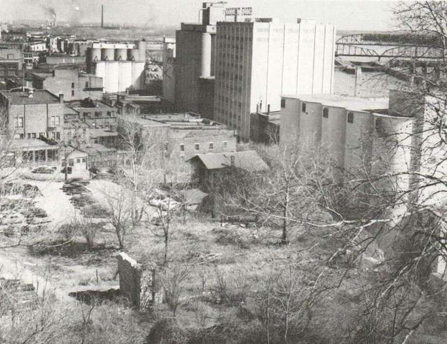 This view of downtown Alton has changed very little through the years. This 1937 photograph shows a partial section of a prison wall still standing, and the Uncle Remus Park city parking lot. In the distance, the Owens-Illinois and American Smelting smokestacks are visible. Much of this land was first claimed by Rufus Easton. Photo: File Photo