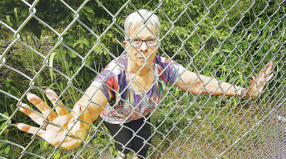 John Badman|The Telegraph Mary Eckhouse, and her husband Dave, are unhappy with the ugly chain-link fencing being installed to keep people off the high speed rail tracks near their house in the 1800 block of Orchard Boulevard in Alton. Fencing is being installed on both sides of the track, up and down the line, making casual pedestrian traffic and shortcuts across the rails on foot impossible.