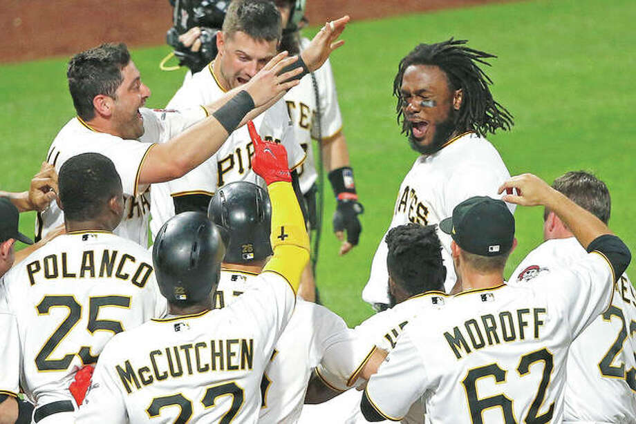 The Pirates' Josh Bell, top right, is swarmed by teammates as he touches the plate after hitting a walk-off three-run home run off Cardinals relief pitcher Seung-Hwan Oh Friday night in Pittsburgh. Photo: AP