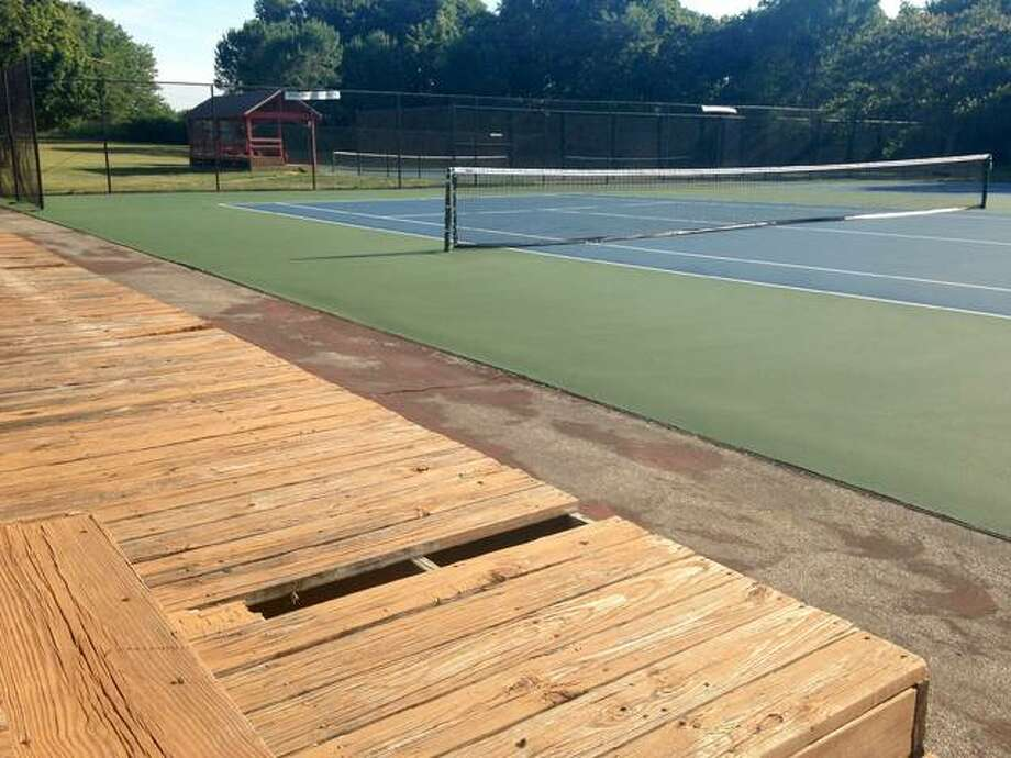"The five newly renovated courts at the Dr. Raymond R. ""Bud"" Simpson Tennis Center in Gordon F. Moore Community Park in Alton are bright blue, framed by green, and ready for play. The common areas, including the walkways and wooden viewing stands, though, still need to be repaired or replaced. Linda N. Weller/The Telegraph"