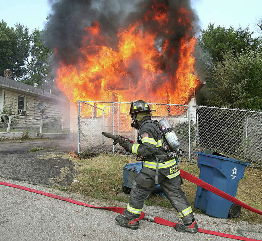 An Alton firefighter pulls a hose into position Tuesday outside 609 Marsh Avenue as flames engulf the front of the house with a young girl still trapped in the basement. It was a tense 10 minutes as firefighters worked to extinguish the fire, reach the girl and police having to restrain family members who wanted to go back in to save her. About 10 minutes into the fire the girl was rescued, virtually uninjured, by Alton firefighters. Photo: John Badman|The Telegraph