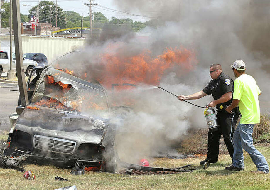 An Alton police officer tries in vain to extinguish a sedan on fire with one adult and one boy inside Thursday on the edge of the KFC parking lot on Landmarks Boulevard. Firefighters arrived soon after. The boy eventually climbed out the vehicle's sun roof and the man was pulled from the driver's seat by firefighters. Both were badly burned. ARCH helicopter ambulances met the victims at local hospitals. Photo: John Badman | The Telegraph