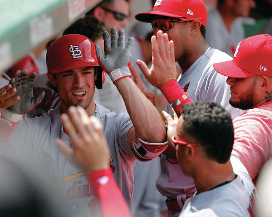 The Cardinals' Randal Grichuk (left) is greeted by teammates in the dugout after hitting a run off Cubs pitcher Jake Arrieta in the second inning Friday in Chicago. Photo: Associated Press