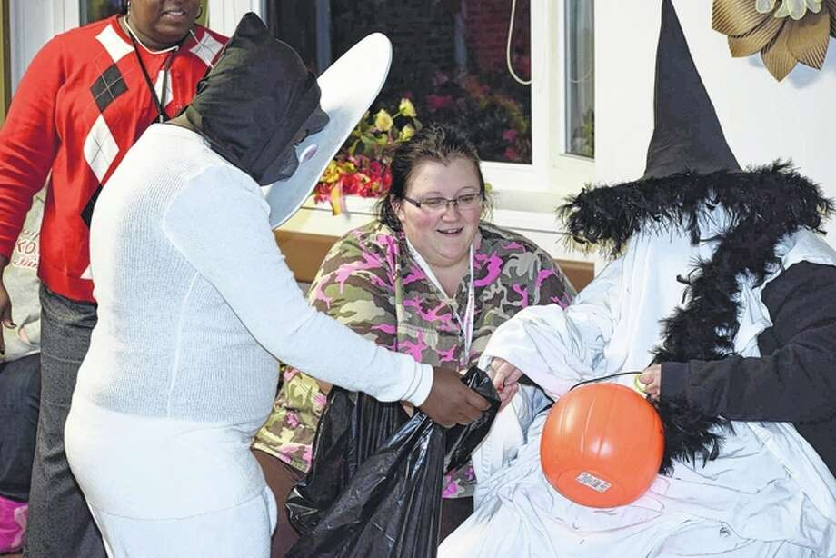 A trick-or-treater gets candy from a Prairie Village Healthcare Center resident Thursday evening at the nursing home's annual Safe Trick or Treating event. About 80 costumed children attended the event. Photo: Greg Olson | Journal-Courier