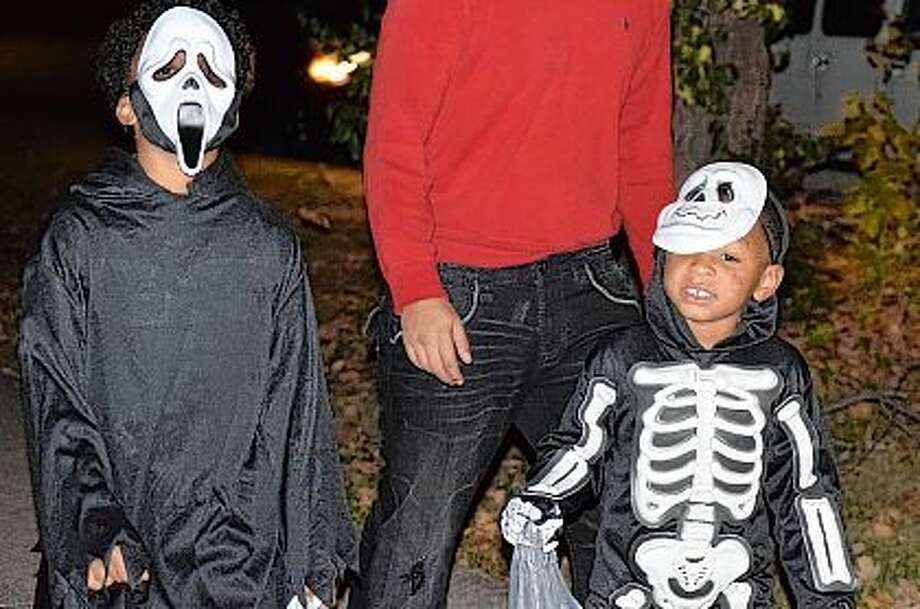 Camren Meredith, 8, and Ca'marion Jackson, 4, of Jacksonville, trick-or-treat along West State Street Friday. The Jacksonville Police Department recommends that children trick-or-treat between 6 and 9 p.m. tonight. Photo: Samantha McDaniel-Ogletree | Journal-Courier