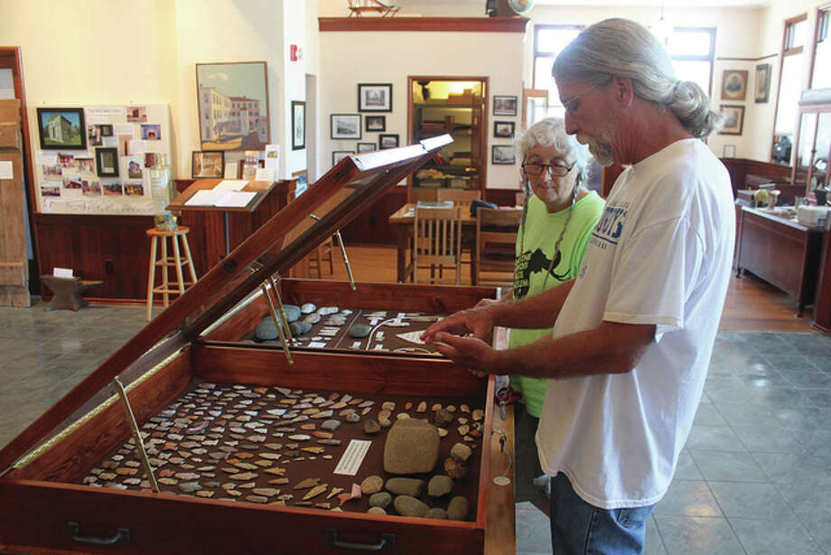 Robert Hickson, assistant coordinator of the Western Illinois Field Station of the Illinois State Archaeological Survey/Prairie Research Institute, looks over arrowheads in the Old School Museum collection with museum docent Janis Dappert.