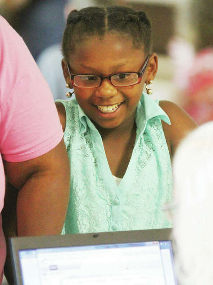 Jayda Holoman, 10, watches as she is registered for fifth-grade at North Elementary School during elementary and middle school registration Tuesday in The Commons at Alton High School. Photo: Scott Cousins Photos | The Telegraph