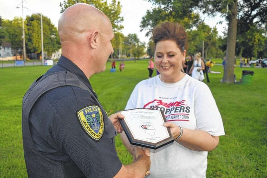 On behalf of the Jacksonville Police Department, Lt. Eric Hansell receives the Morgan-Scott Crimestoppers' Contributor of the Year Award from Jen Brainerd, vice president of Morgan-Scott Crimestoppers, Tuesday night at Jacksonville's first National Night Out event in Community Park. Photo: Greg Olson | Journal-Courier