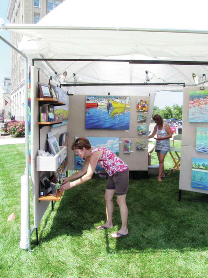 A patron (left) of a past year's Art Fair on the Square looks at art for sale in a tent run by artist Terri Meyer (back right) of Missouri. The art fair, a project of Jacksonville Main Street, returns to the square Friday and Saturday. Photo: Submitted Photo