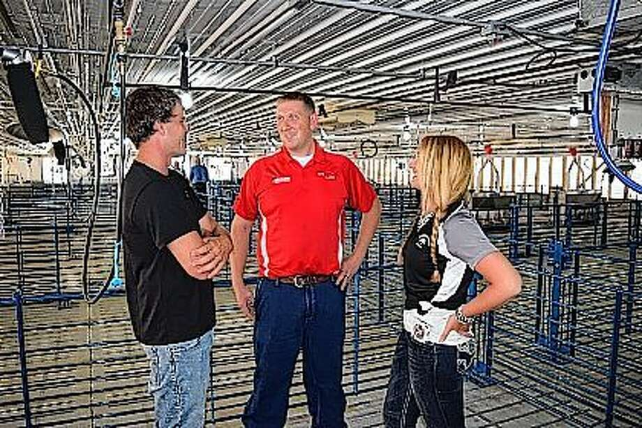 Alex Winkelman (left) talks with Shawn Beck of Beard Implement Co. and Shayla Allen Thursday at the opening of a new 2,400-head wean-to-market hog barn on the Winkelman family farm northeast of Concord. Dale Winkelman and his son Alex will be contracting with The Maschhoffs, a family-owned pork producer based in Carlyle, to raise small pigs to market size. Photo: Greg Olson | Journal-Courier