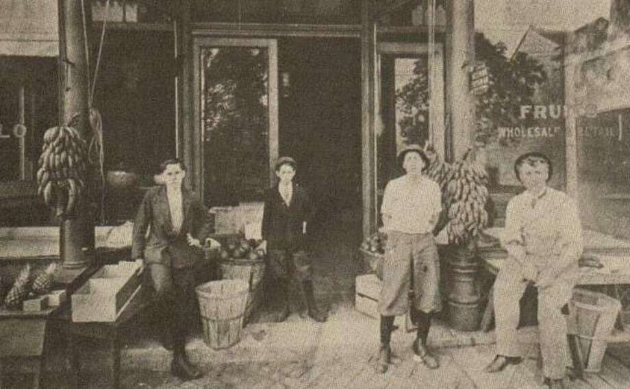The M.A. Crivello Fruit Market was located at 110 E. Broadway, where Godwin's Office Supplies was later located. The market carried local produce as well as that brought in by steamer. Crivello built up a thriving business with local housewives in addition to a wholesale trade. Three of his sons pictured here (on the right) helped out with a variety of chores. The Crivellos had twelve children, many of whom assisted with the family business. Other Crivello families ran similar markets on Piasa Street and Belle Street. Photo: File Photo